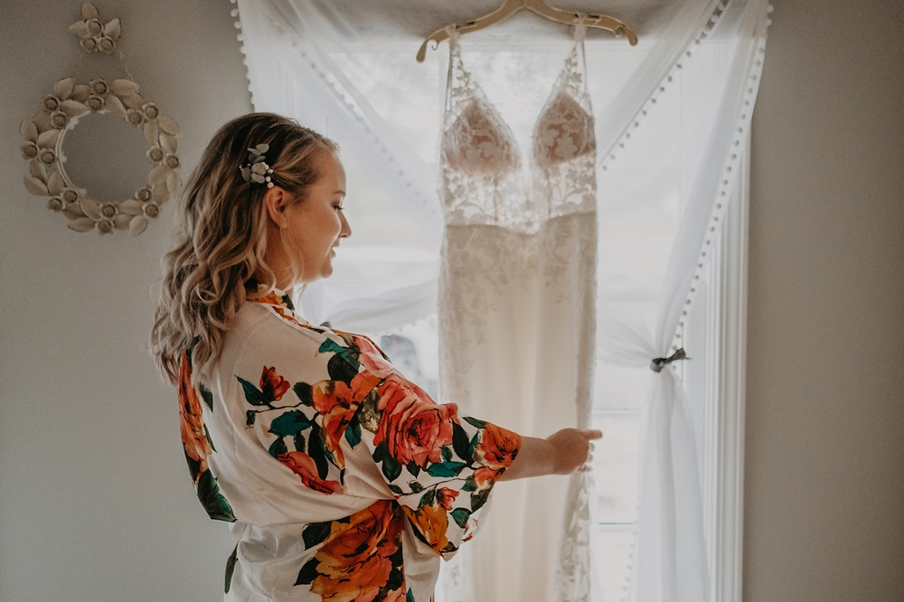 Bride looking at hanging wedding dress. Photographed by Nicole Leanne Photography.