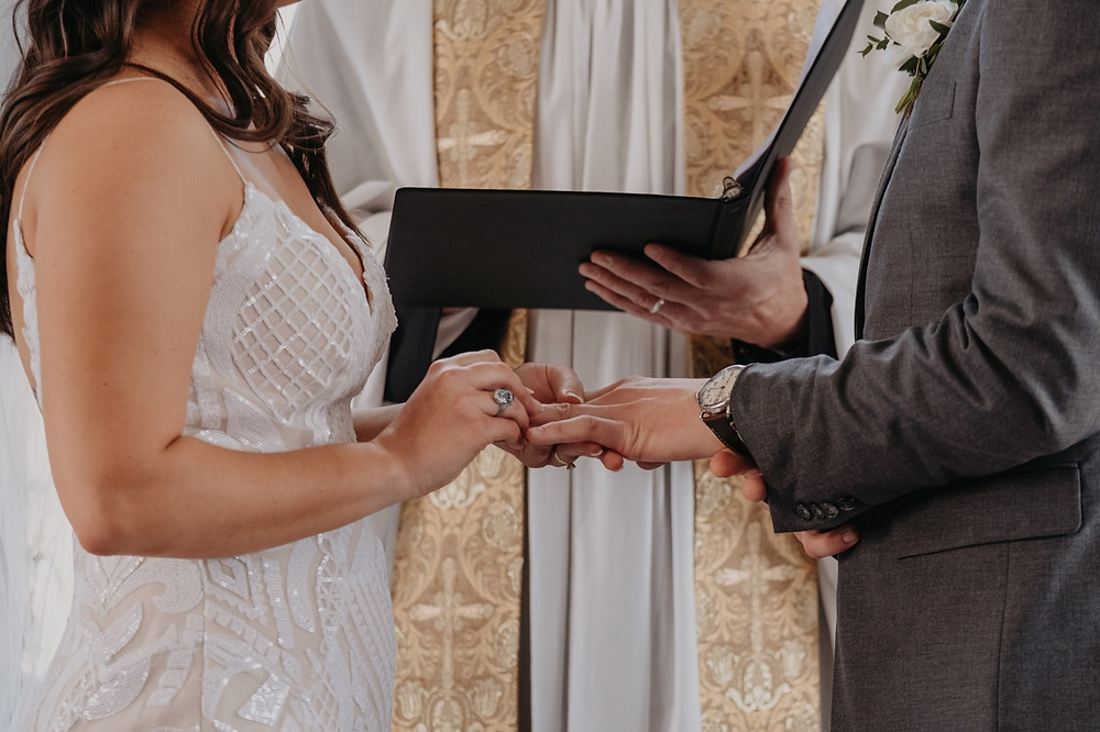 Exchanging of rings during Detroit wedding ceremony. Photographed by Nicole Leanne Photography.