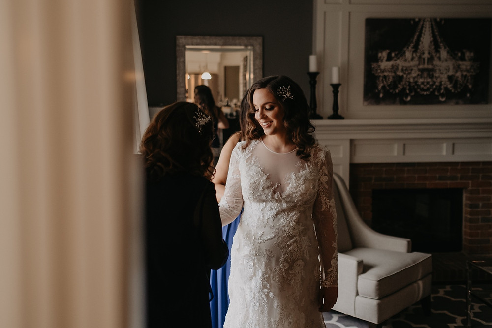 Bride getting dressed on wedding day in Metro Detroit. Photographed by Nicole Leanne Photography.