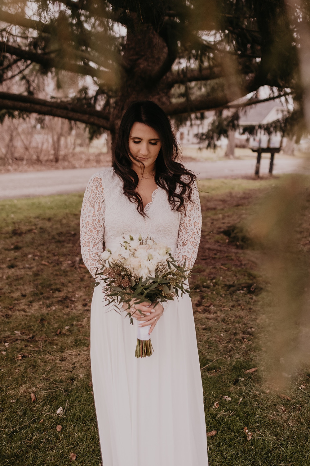 Bride on wedding day holding white bouquet. Photographed by Nicole Leanne Photography