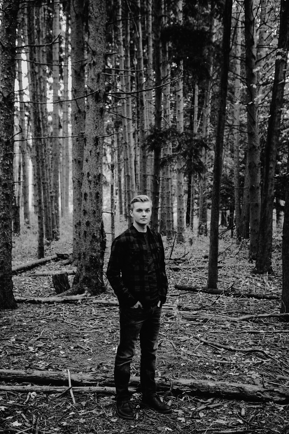 senior portrait, male standing in woods