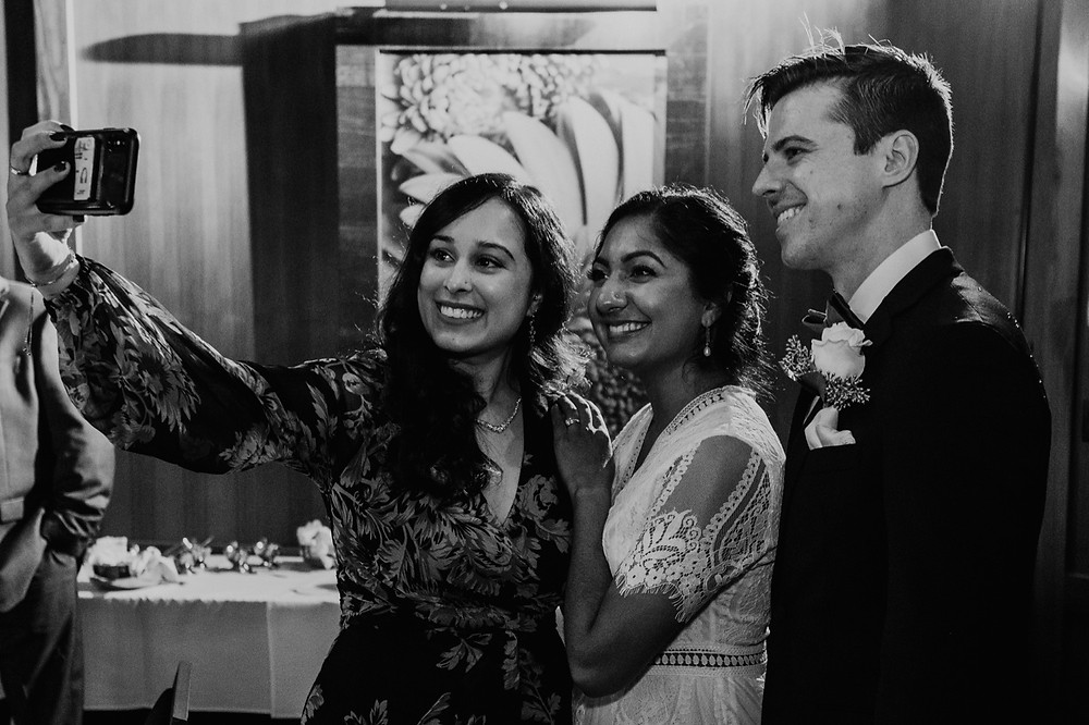 Couple taking photos with wedding guests at reception. Photographed by Nicole Leanne Photography.
