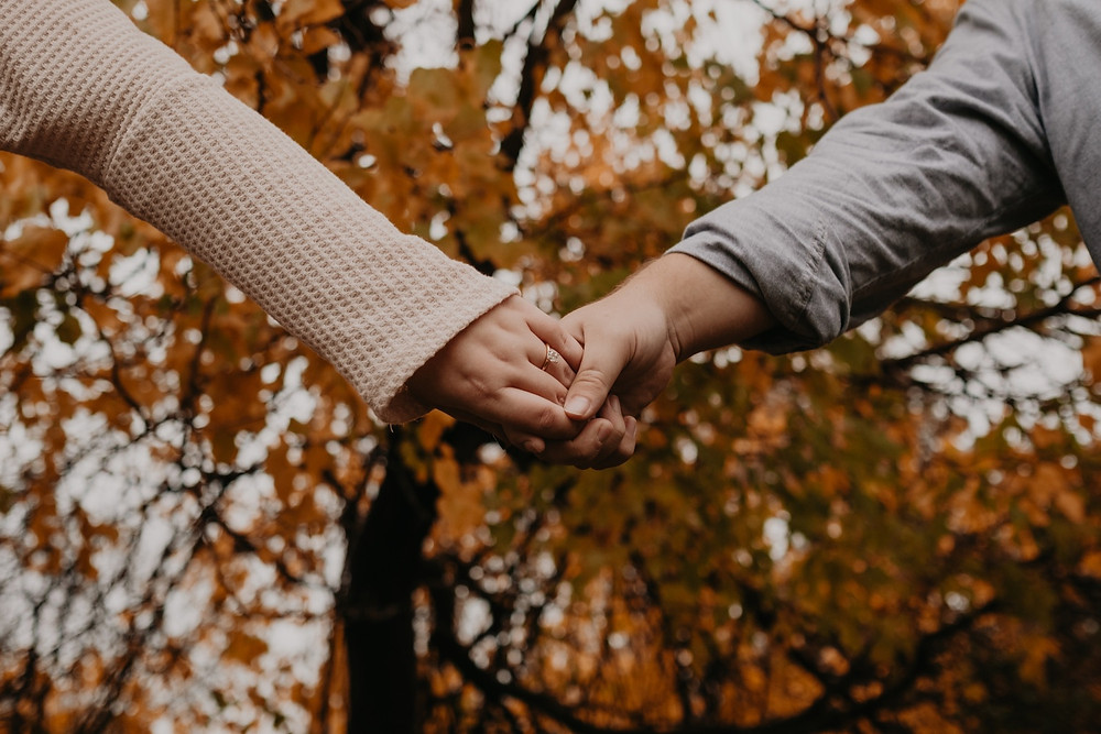 Couple holding hands with fall leaves in background. Photographed by Nicole Leanne Photography.