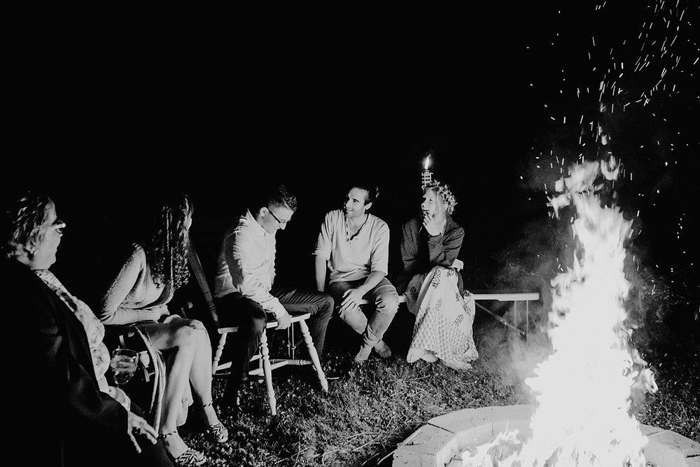 bride and groom sitting around fire