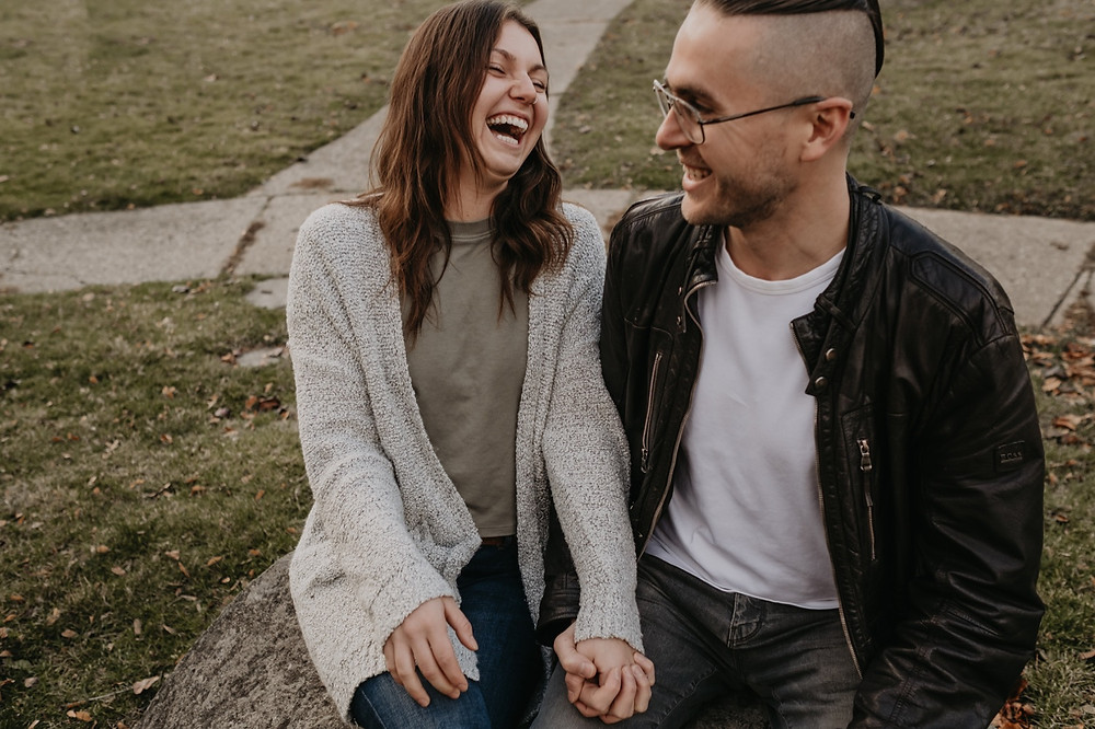Laughing couple during casual engagement photos. Photographed by Nicole Leanne Photography.