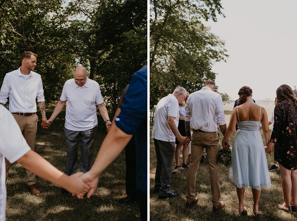 Prayer circle with wedding guests at park wedding in Metro Detroit. Photographed by Nicole Leanne Photography.