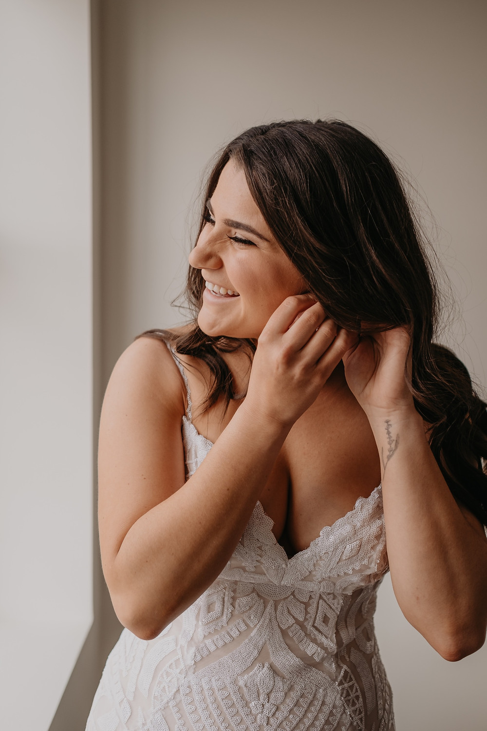 Bride putting on earrings for wedding day. Photographed by Nicole Leanne Photography.