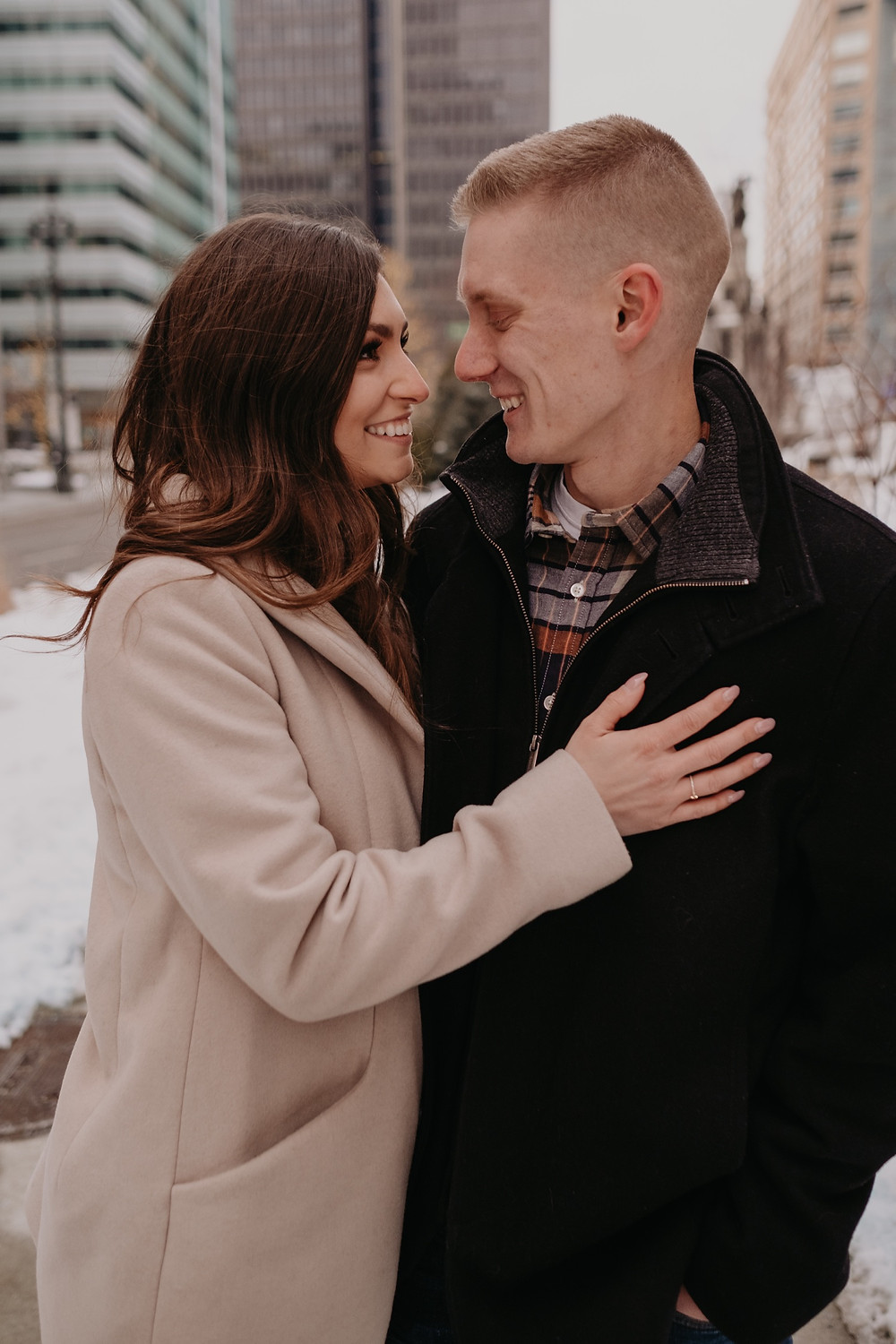 Couple posing for engagement photos in Downtown Detroit. Photographed by Nicole Leanne Photography.