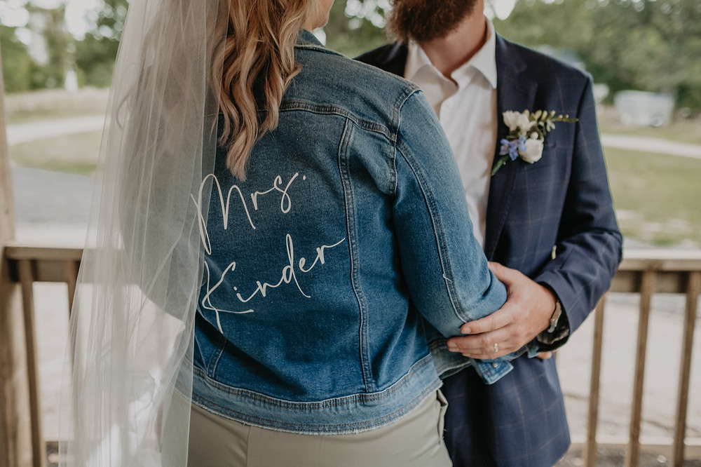 Bride wearing jean jacket over wedding dress. Photographed by Nicole Leanne Photography.