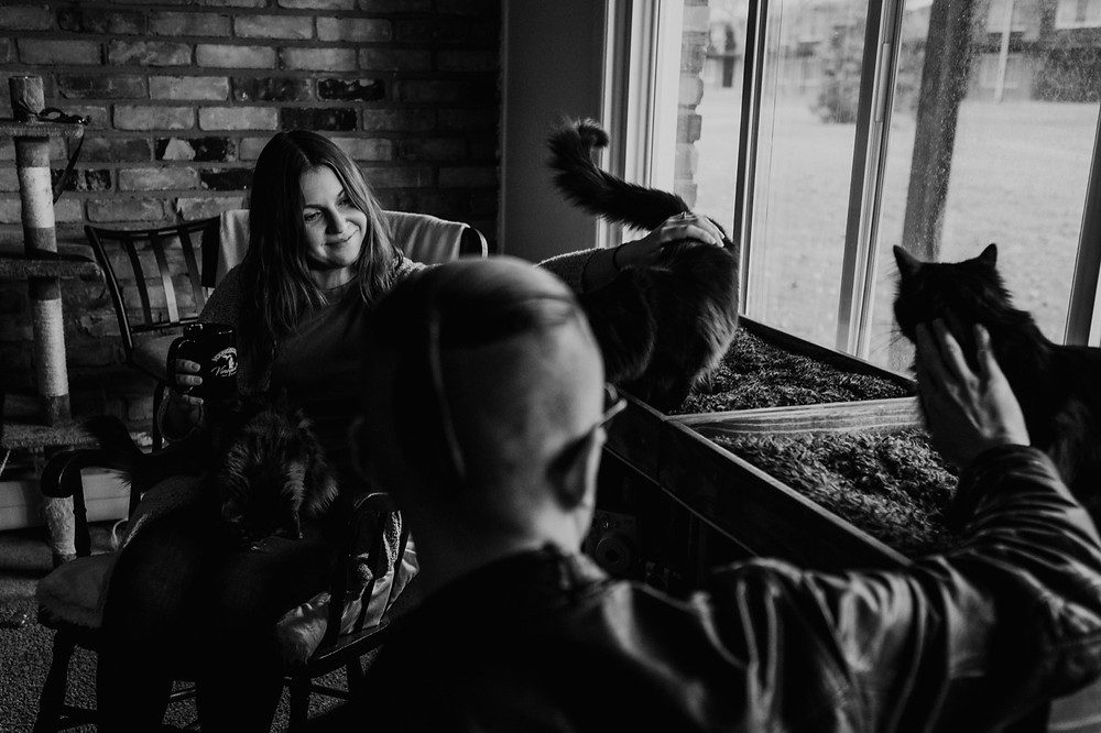 Black and white photo of couple with cats at home engagement session. Photographed by Nicole Leanne Photography.
