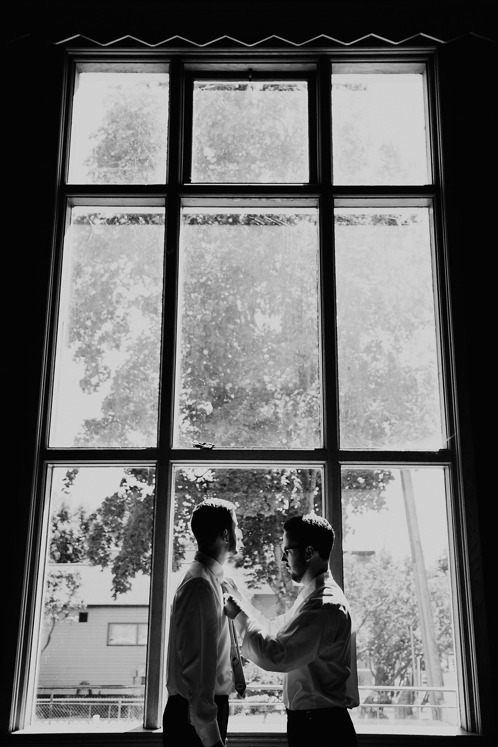 Silhouette photo in black and white of groom and best man. Photographed by Nicole Leanne Photography.
