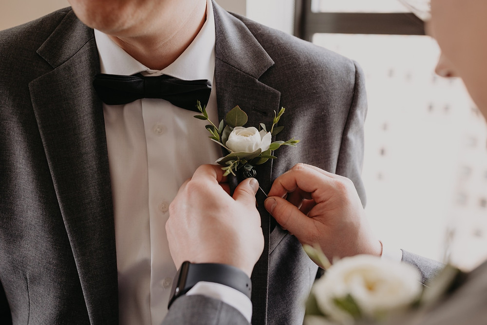 Wedding day boutonniere pinning on the groom. Photographed by Nicole Leanne Photography.