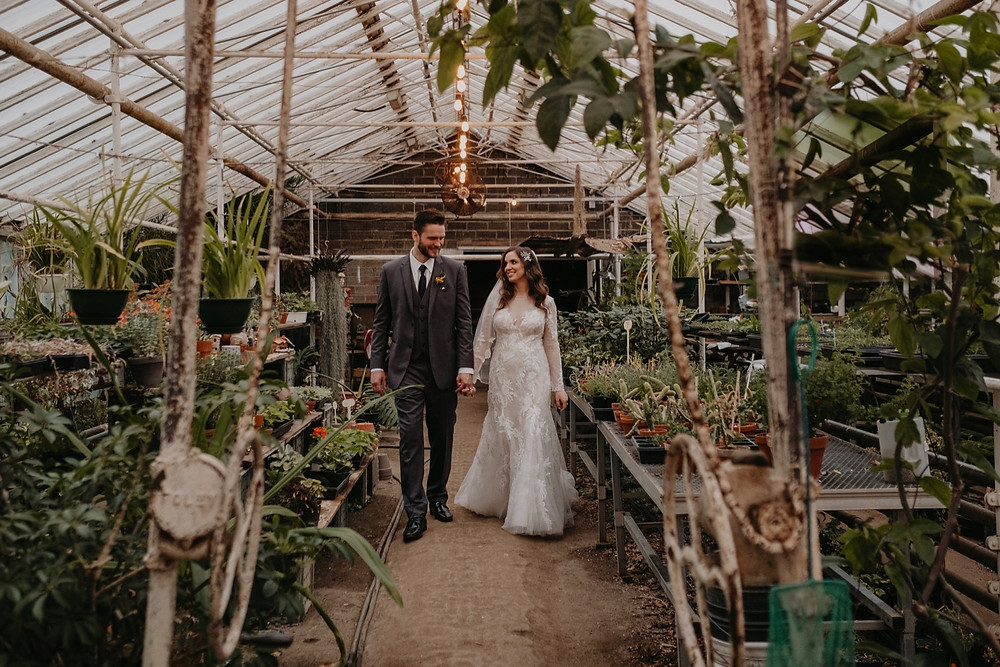 Bride and groom surrounded by plants in greenhouse wedding. Photographed by Nicole Leanne Photography.