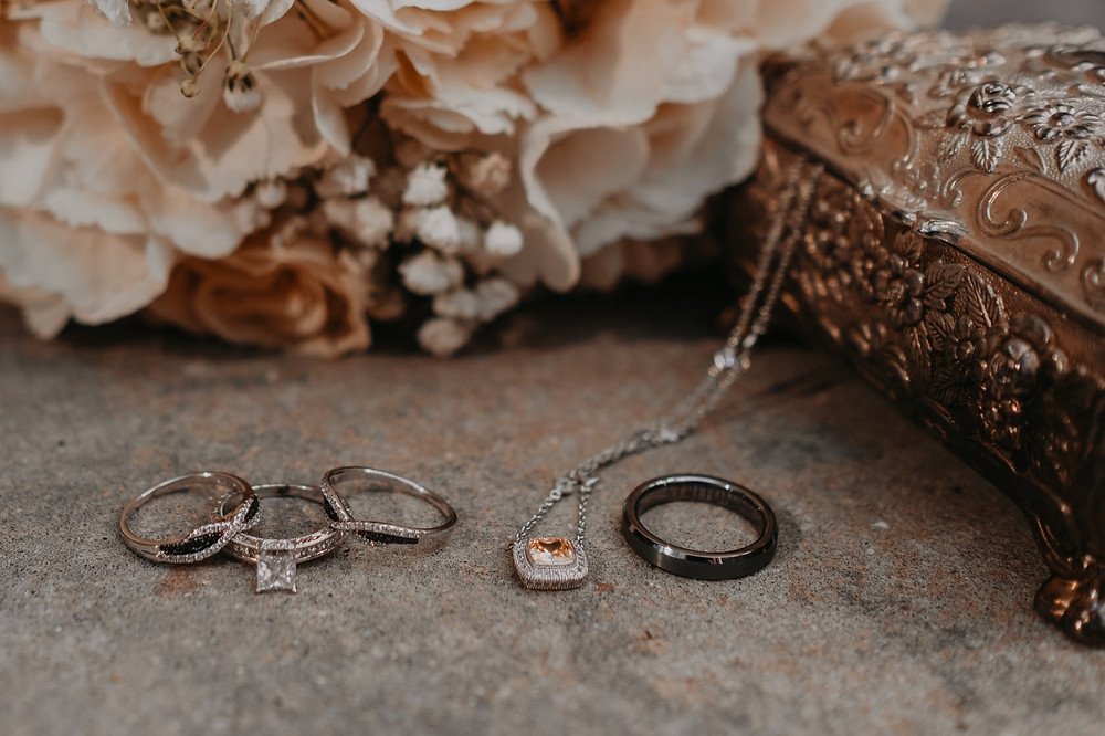 Fall wedding details with jewelry and wedding rings. Photographed by Nicole Leanne Photography.