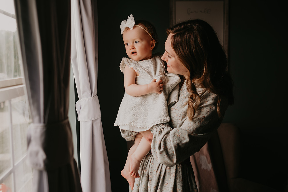 Mother and daughter looking out window at home photo session. Photographed by Nicole Leanne Photography.