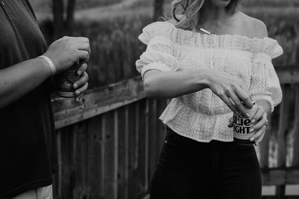 Couple sharing some beers during engagement session. Photographed by Nicole Leanne Photography