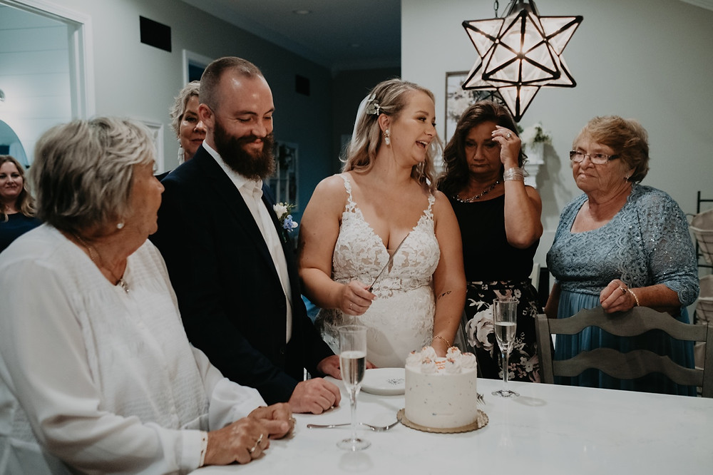 Bride and groom cut cake at small wedding. Photographed by Nicole Leanne Photography.