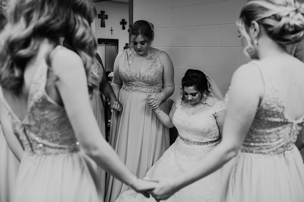 Prayer circle with brides and bridesmaids. Photographed by Nicole Leanne Photography.