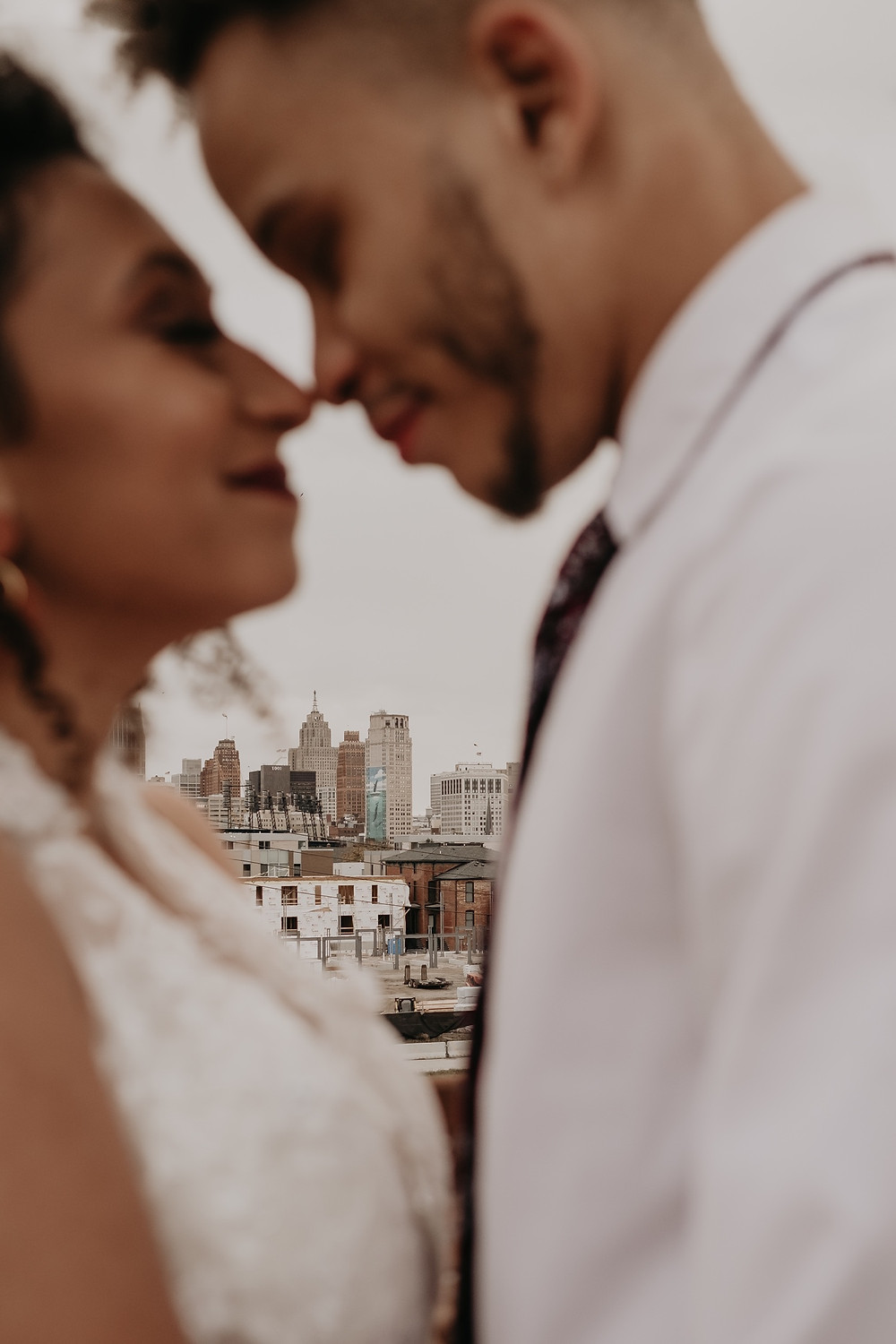 Bride and groom kiss with Detroit skyline in the background. Photographed by Nicole Leanne Photography.