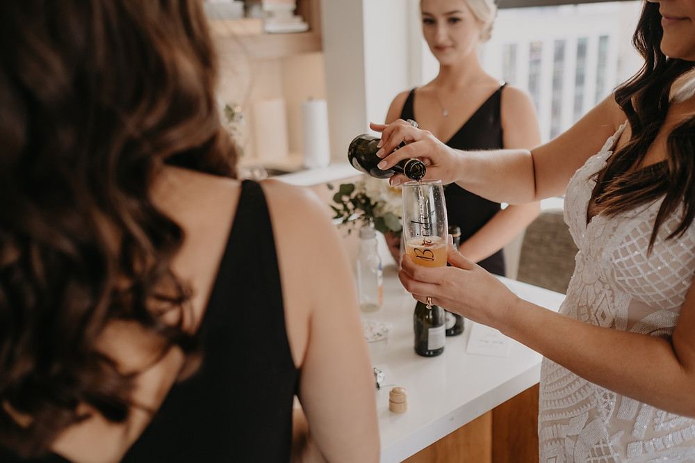 Bridesmaid sharing champagne with bride on wedding day. Photographed by Nicole Leanne Photography.
