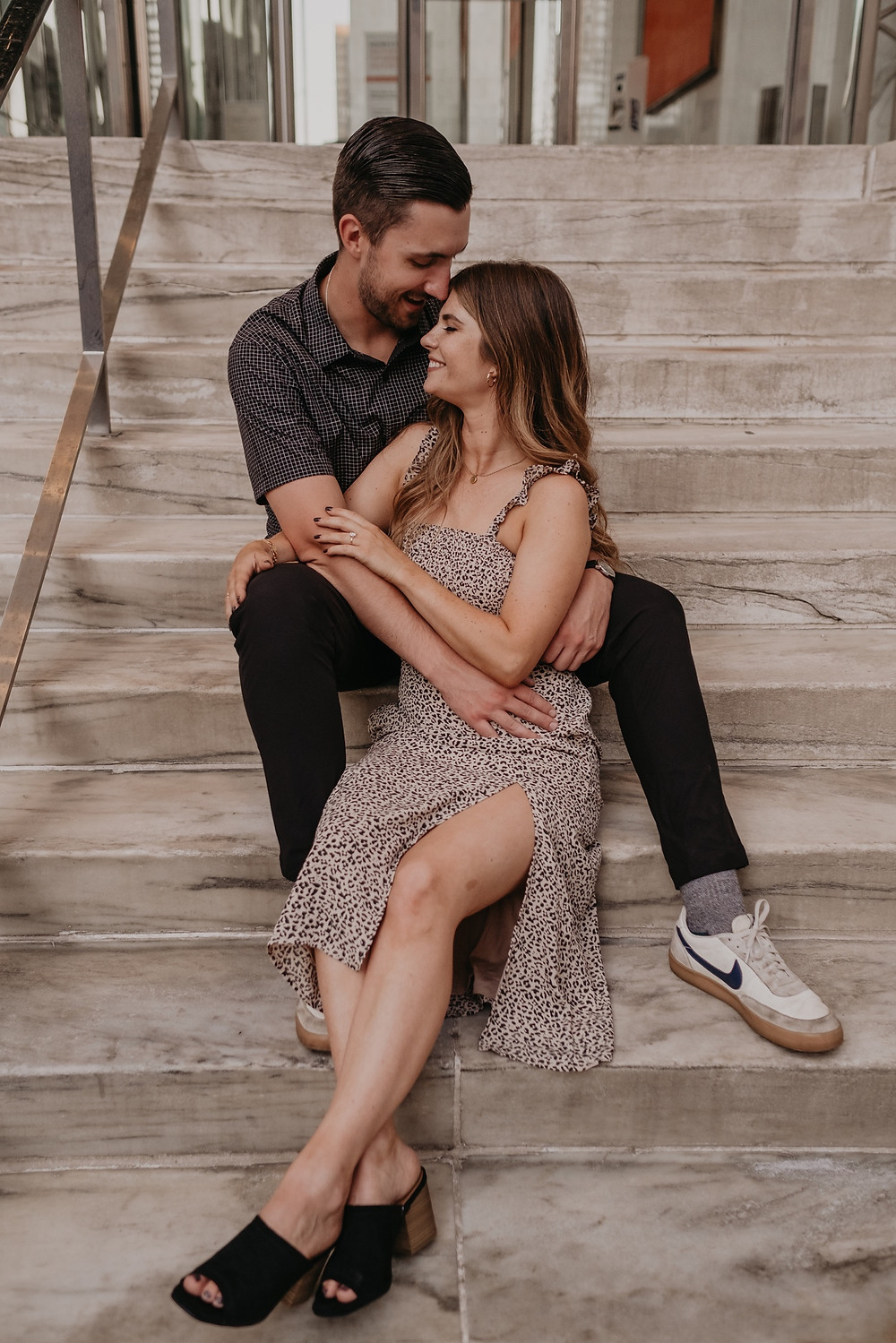Couple sitting on marble steps in Detroit engagement session. Photographed by Nicole Leanne Photography.