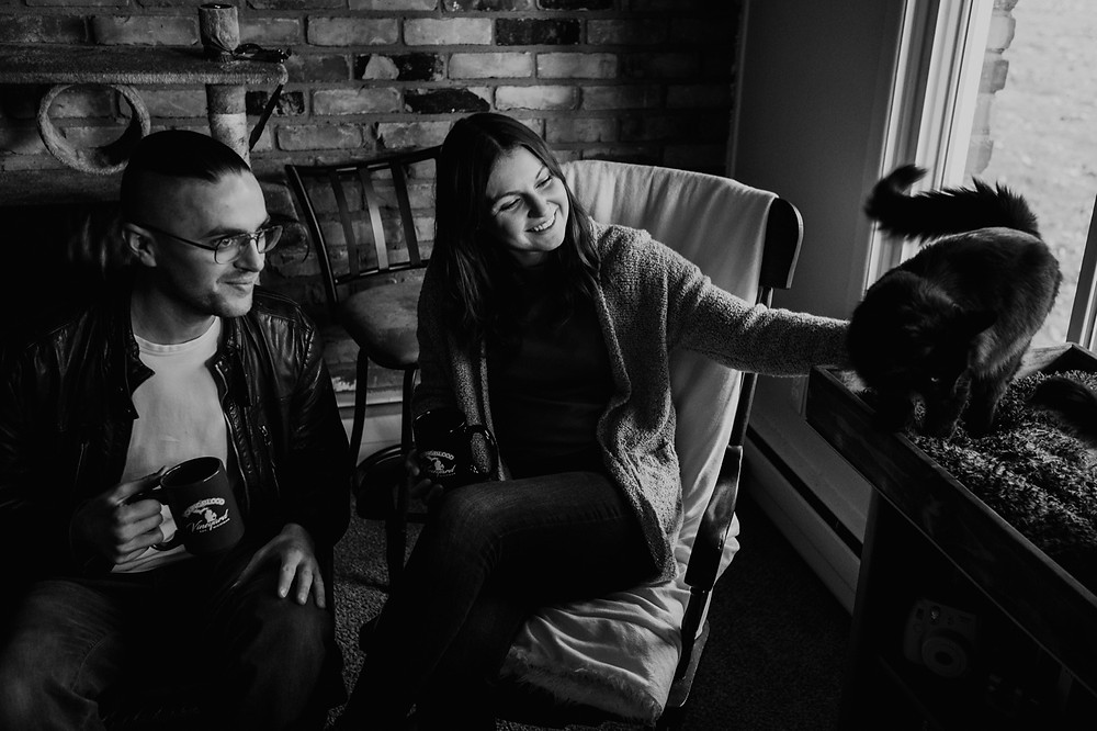 Black and white photo of couple with cats during home engagement session. Photographed by Nicole Leanne Photography.