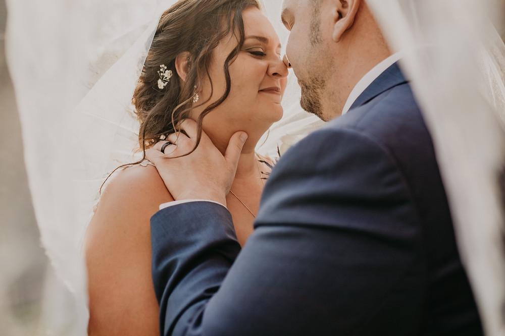 Michigan bride and groom embrace on wedding under veil