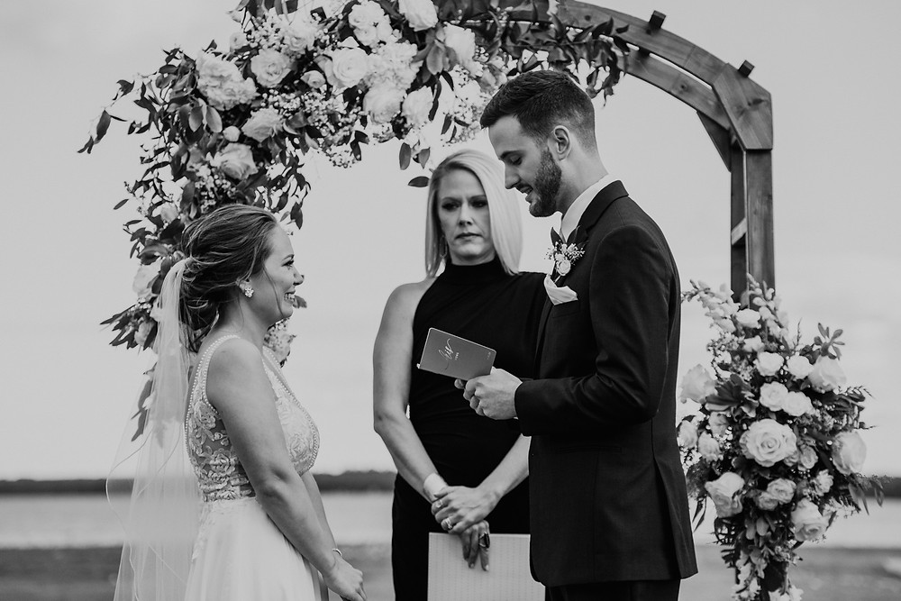 Groom reading vows at altar during wedding ceremony. Photographed by Nicole Leanne Photography.