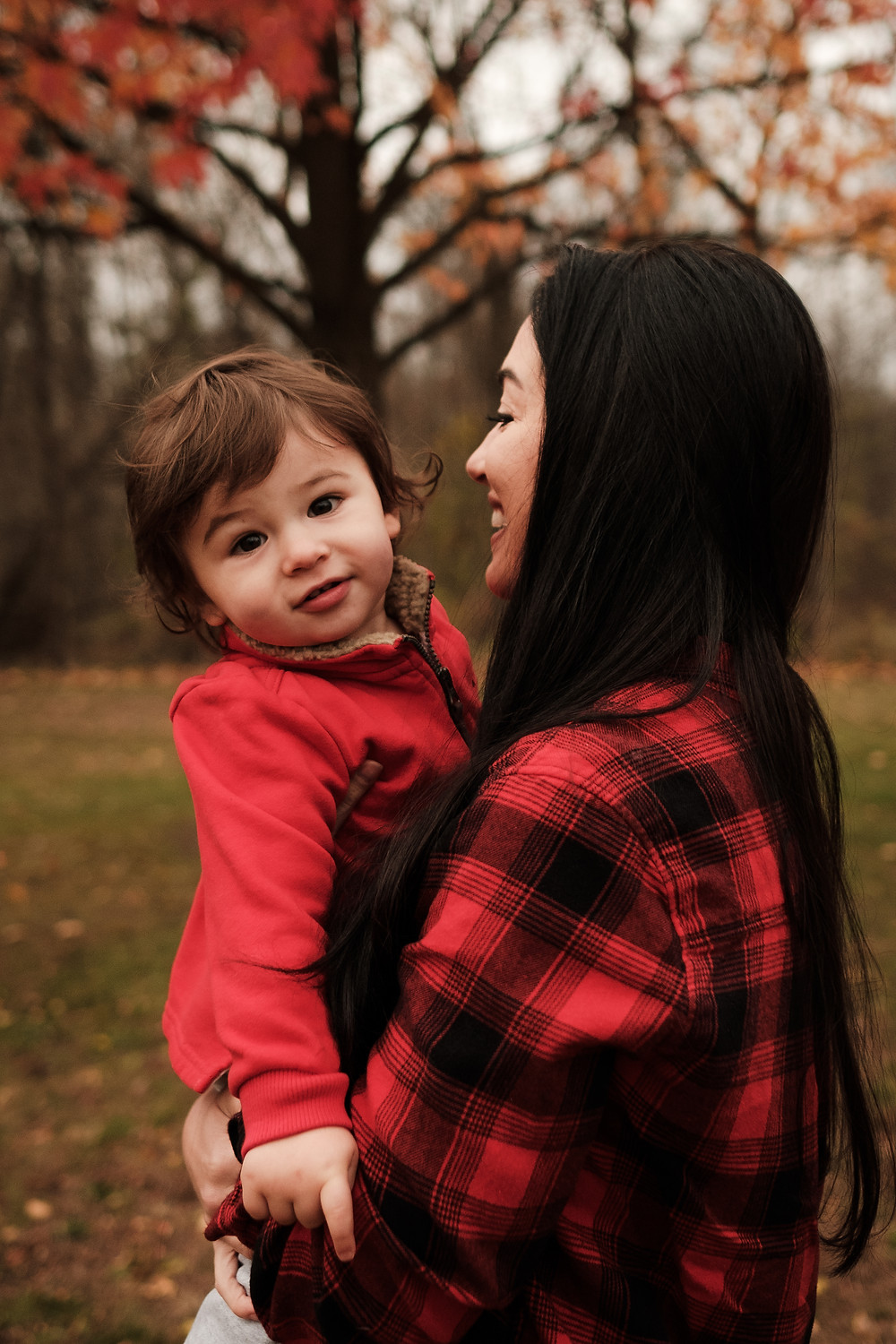 mother smiles holding son, fall leaves