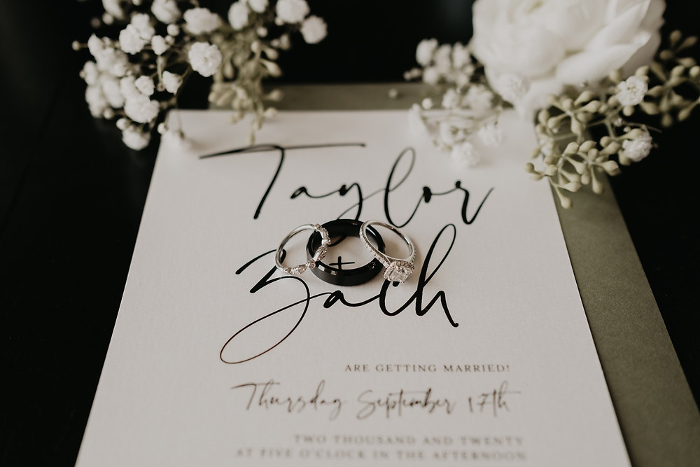 Wedding stationary with rings and florals. Photographed by Nicole Leanne Photography.