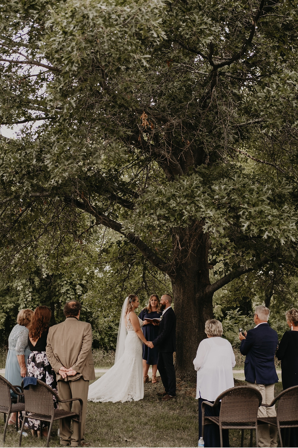 Bride and groom getting married under a tree in Metro Detroit. Photographed by Nicole Leanne Photography.