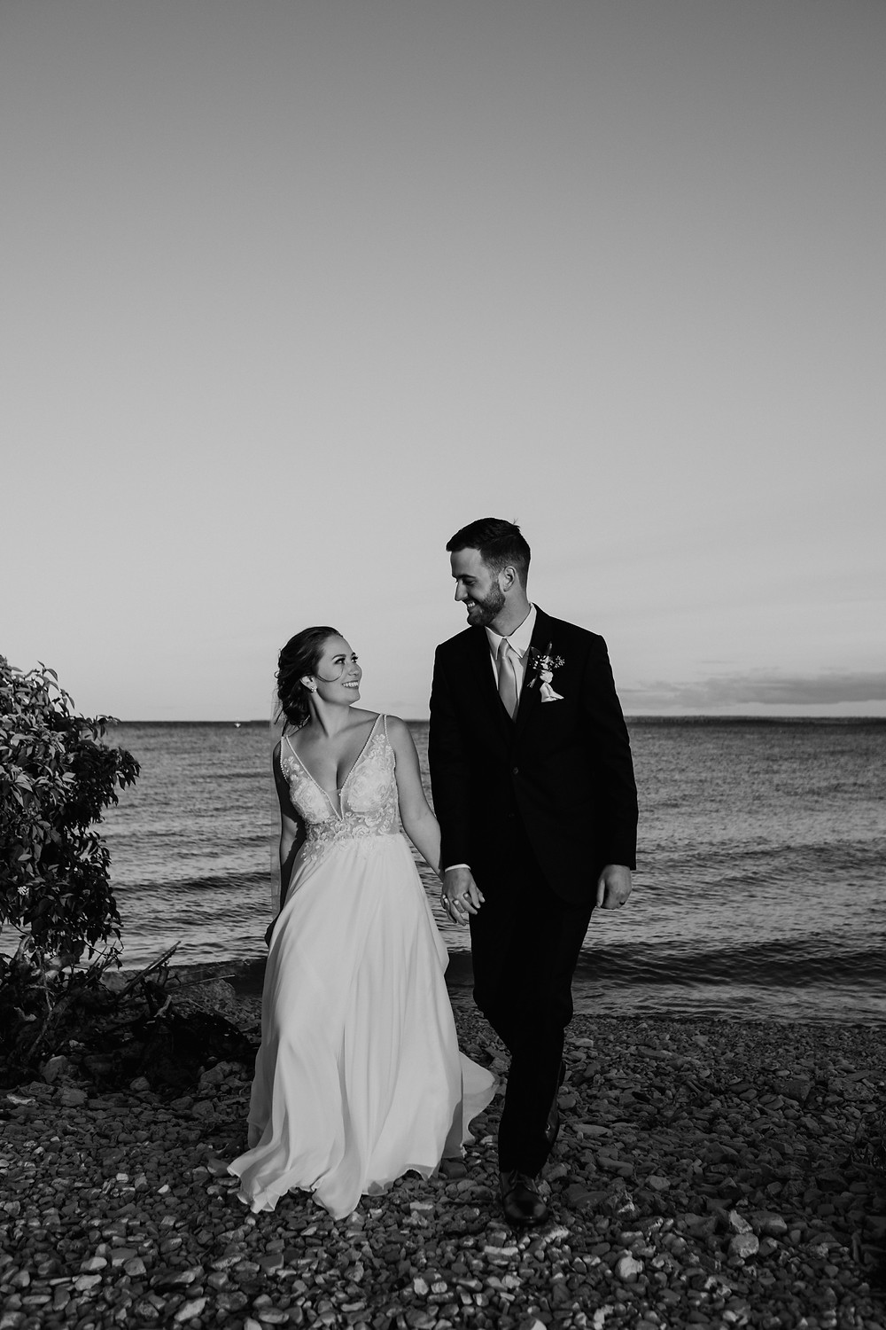 Bride and groom by lake on wedding day. Photographed by Nicole Leanne Photography.