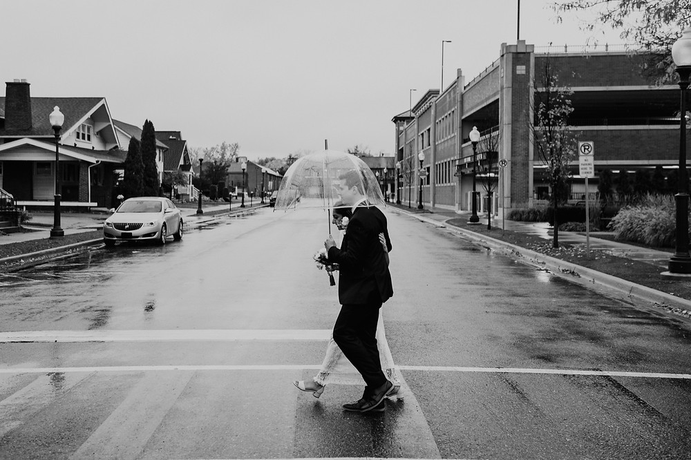 Bride and groom walking crosswalk in Metro Detroit. Photographed by Nicole Leanne Photography.