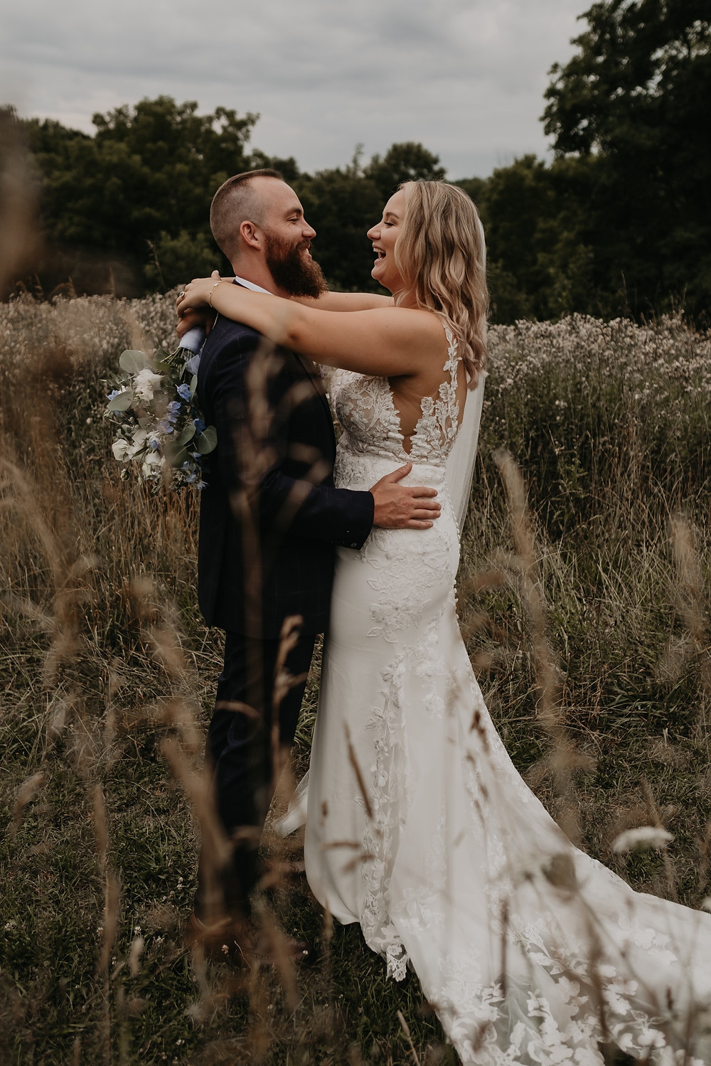 Bride and groom dancing in field on wedding day. Photographed by Nicole Leanne Photography.
