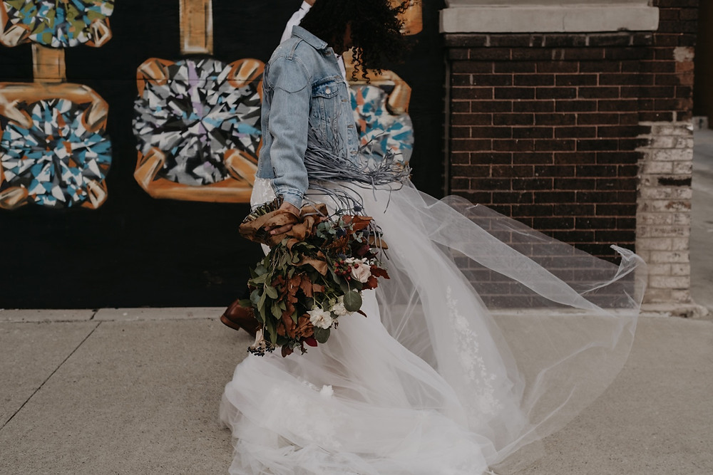 Bride walking on sidewalk in Downtown Detroit, Michigan. Photographed by Nicole Leanne Photography.