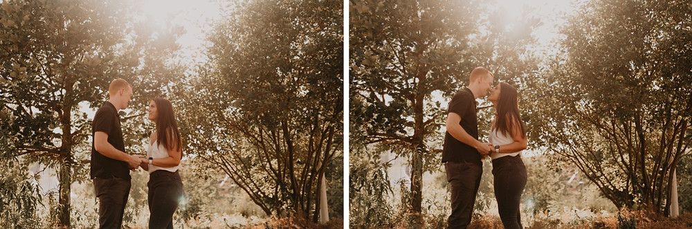 Sunlight peeking through trees as couple kisses after proposal. Photographed by Nicole Leanne Photography