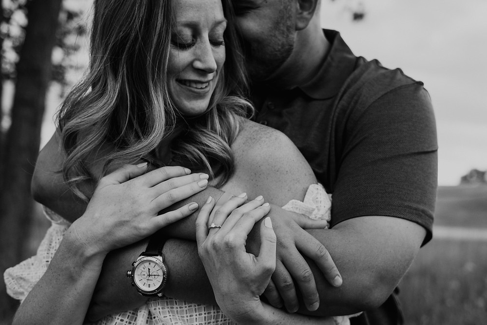Black and white photo of man hugging woman at engagement session in Metro Detroit. Photographed by Nicole Leanne Photography