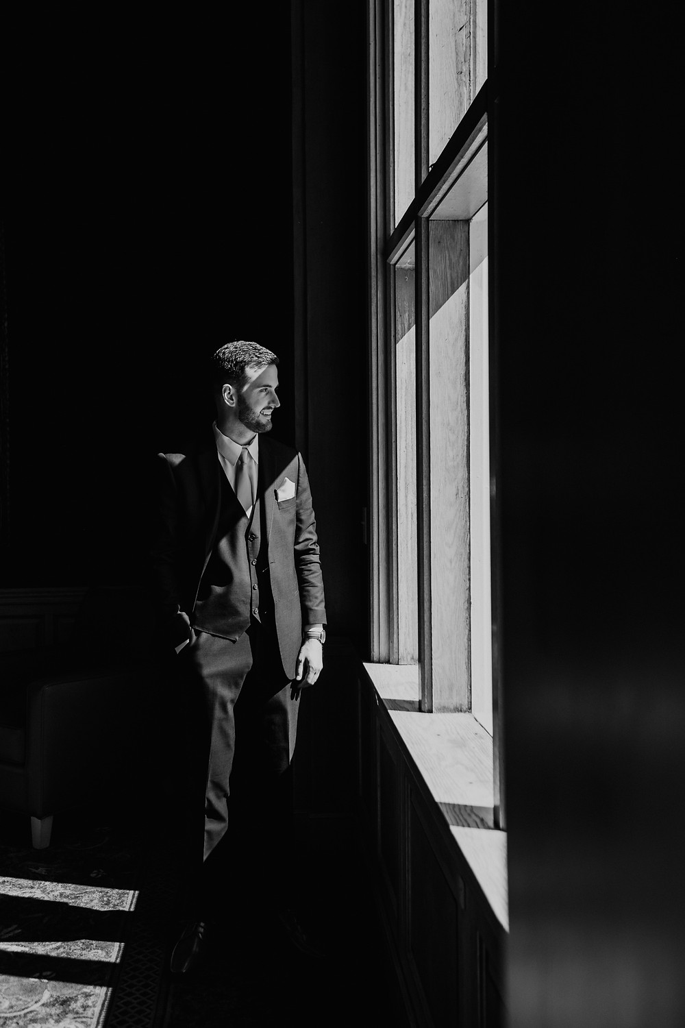 Black and white photo of groom looking out window in Detroit, Michigan. Photographed by Nicole Leanne Photography.