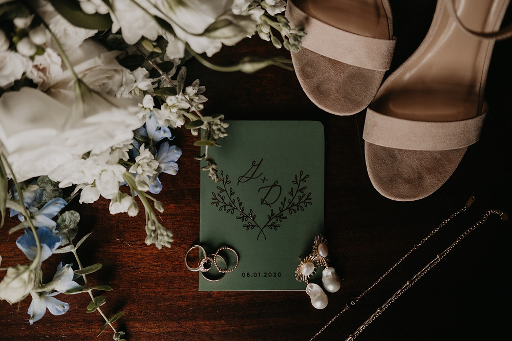 Flatlay of wedding details and jewelry. Photographed by Nicole Leanne Photography.