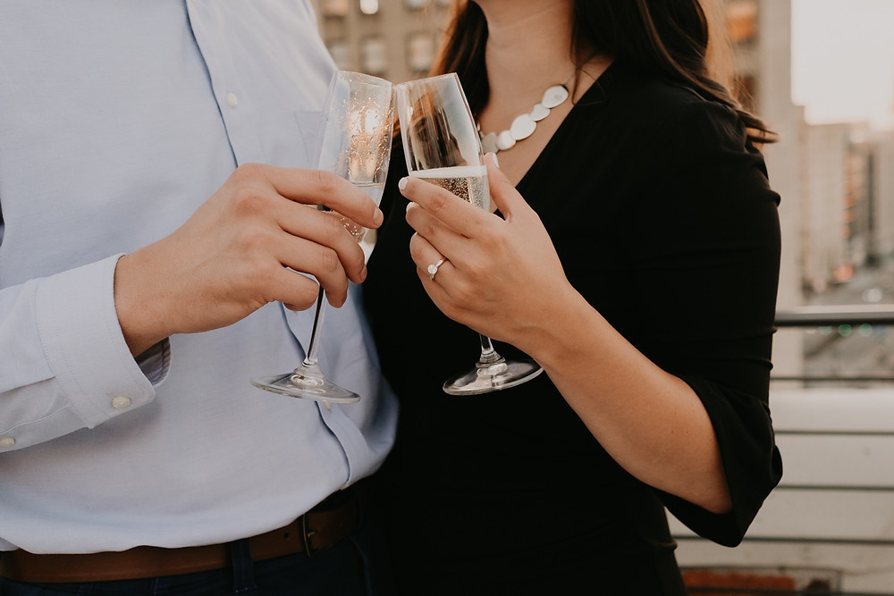 Couple toasts with champagne at rooftop of The Monarch Club. Photographed by Nicole Leanne Photography.