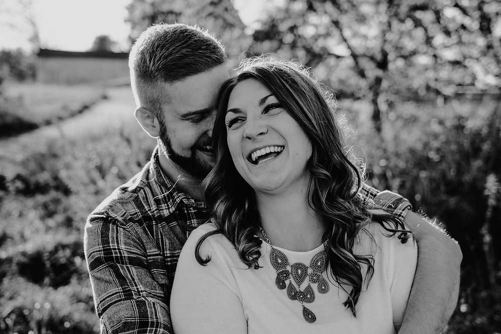 Couple hugging in field for engagement photos. Photographed by Nicole Leanne Photography.
