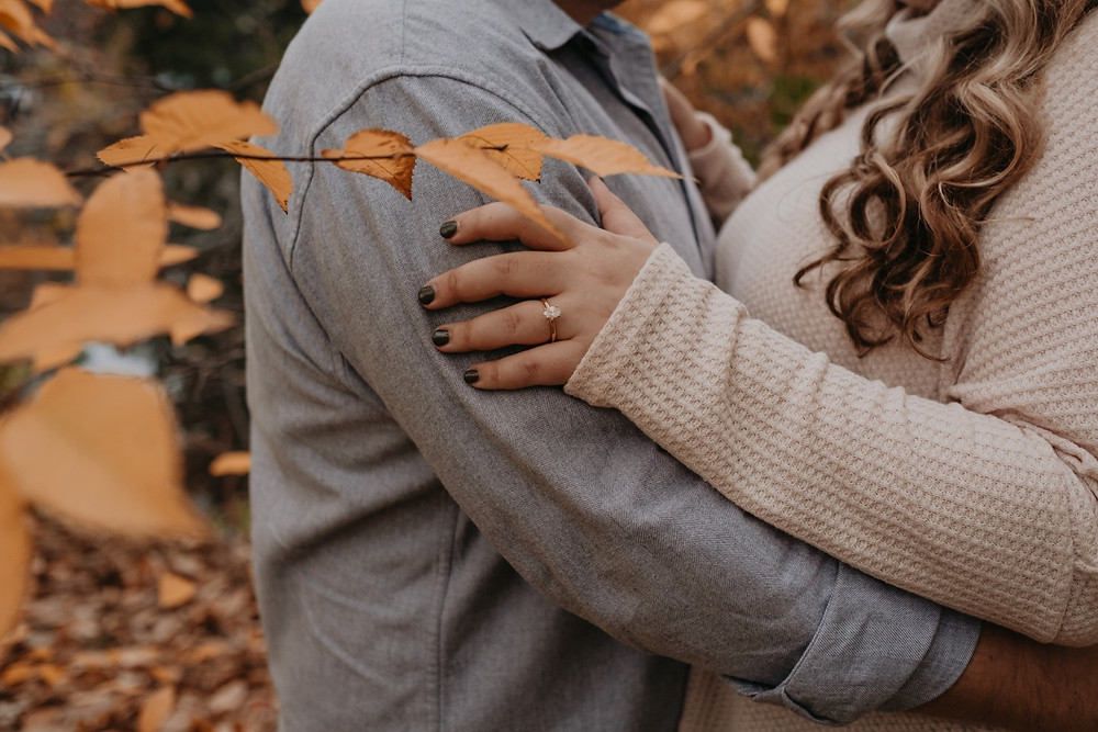 Close up of wedding ring during fall engagement photos. Photographed by Nicole Leanne Photography.