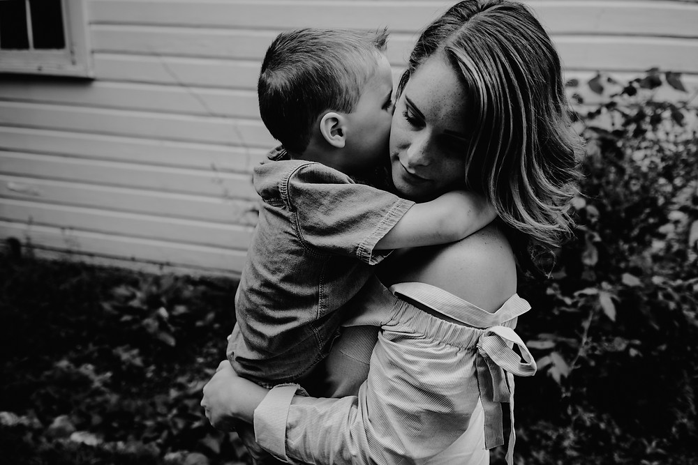 Mother holding child in backyard in black and white. Photographed by Nicole Leanne Photography.