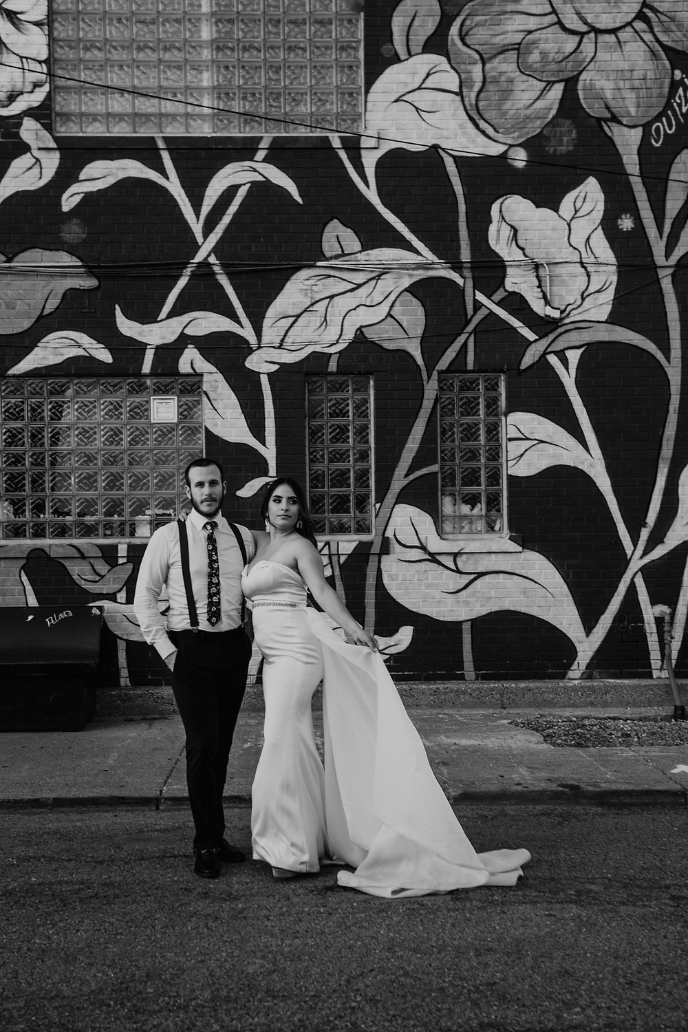 Bride and groom taking wedding photos with Detroit murals. Photographed by Nicole Leanne Photography.
