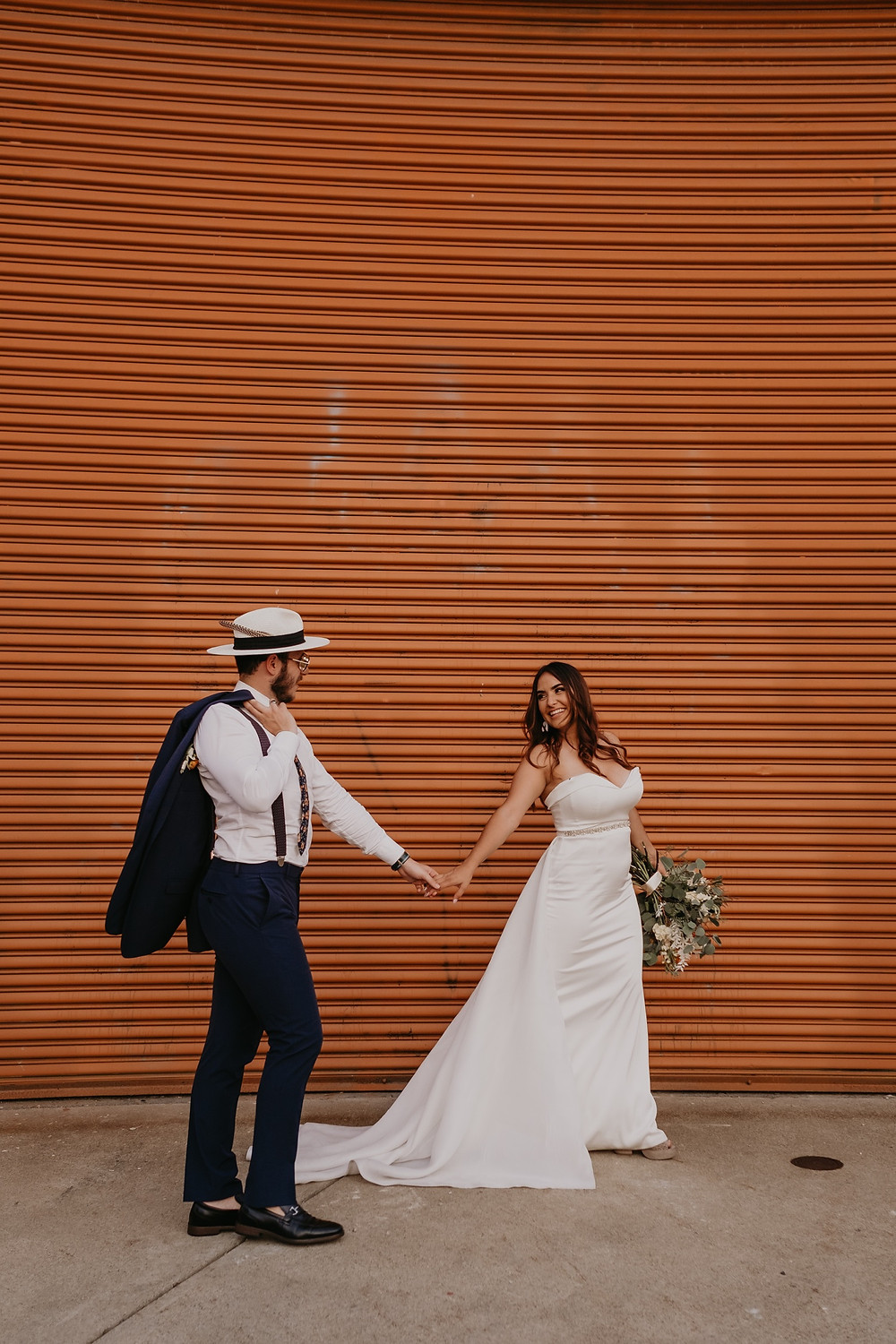 Bride and groom walking in Downtown Detroit at Eastern Market. Photographed by Nicole Leanne Photography.