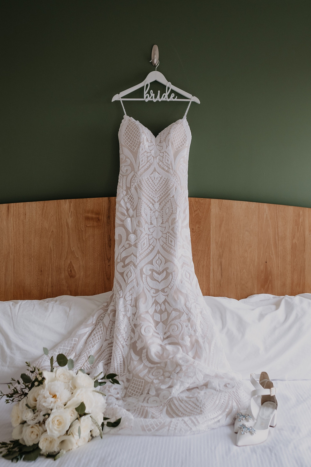 Wedding dress hanging on bride hanger. Photographed by Nicole Leanne Photography.
