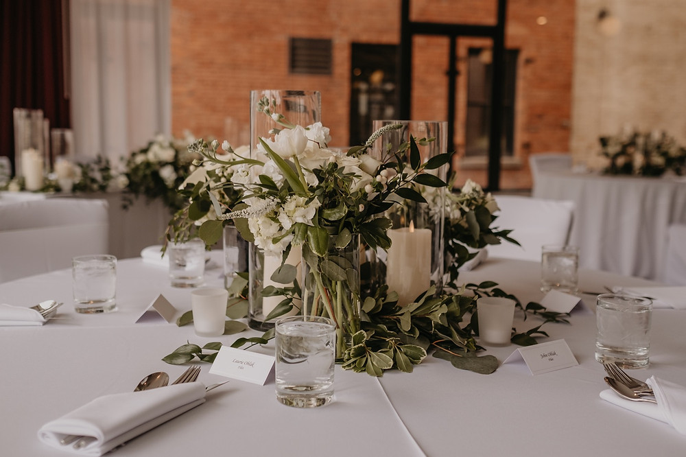 Wedding centerpieces with greenery and white flowers. Photographed by Nicole Leanne Photography.