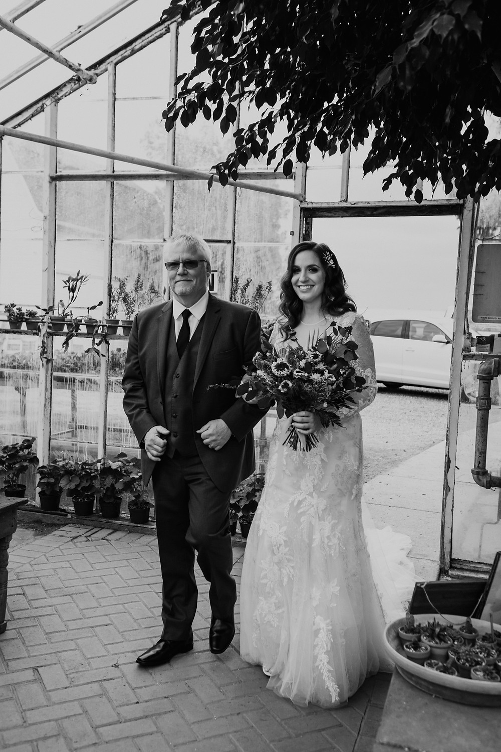 Bride walking down aisle of greenhouse wedding. Photographed by Nicole Leanne Photography.