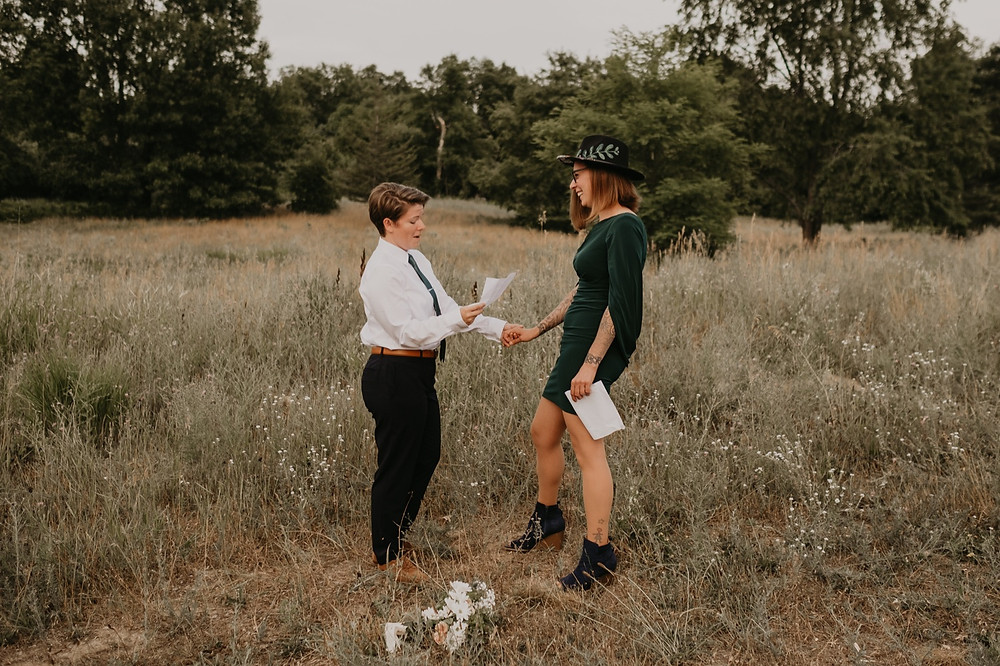 Reading vows at commitment ceremony in Stony Creek Metro Park. Photographed by Nicole Leanne Photography