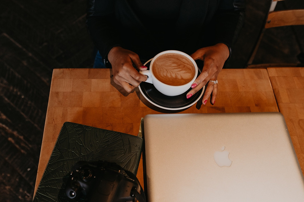 Close up of woman holding latte in coffee shop with laptop on table.
